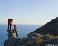 An Hispanic couple is climbing a rock outcropping overlooking the vast ocean below. Boyfriend is helping his girlfriend up to the top of the rock he is standing on. Dangerous looking undertaking requiring great skill and team work.